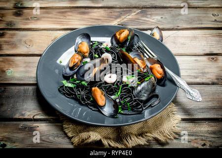 La comida mediterránea. Espaguetis con tinta negra de sepia y almejas. Sobre un fondo de madera.