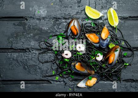 La comida mediterránea. Espaguetis con tinta de sepia y almejas. Negro sobre fondo rústico.