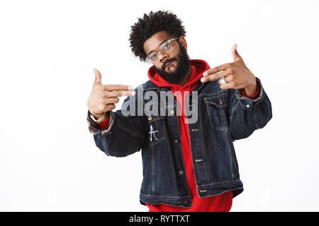 Enfriar y stlyish guapo macho joven afroamericano rapero con barba y piercing mostrando gestos de pistola de dedos apuntando a sí mismo, lamiendo los labios y