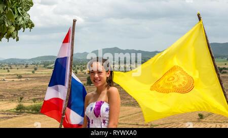 Teen parado entre el tailandés y el templo banderas en día ventoso con campos y montañas en la parte trasera del terreno