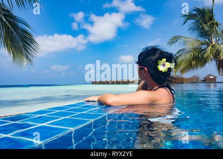 Chica contemplando el océano mientras está sentado al lado de la piscina Foto de stock