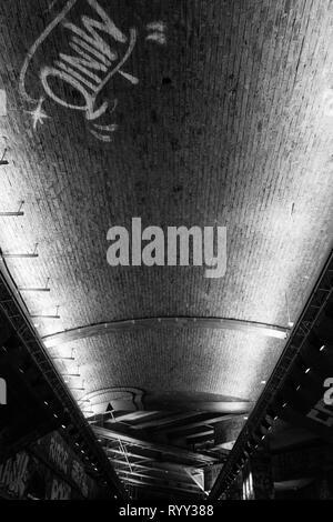 En blanco y negro de impresión urbano arquitectónico. Arco de Ladrillo iluminadas desde abajo - London UK