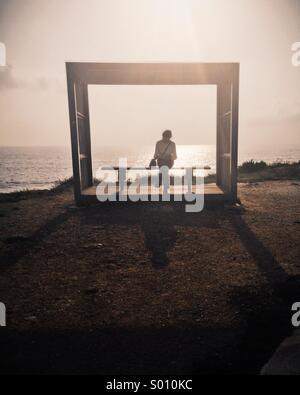 Una solitaria mujer sentada en un banco en el mar