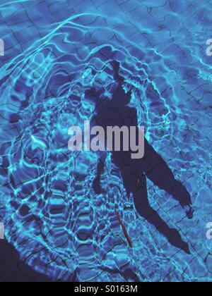 Sombra de un nadador en el fondo de una piscina