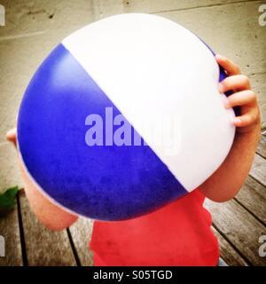 Kid sosteniendo pelota de playa