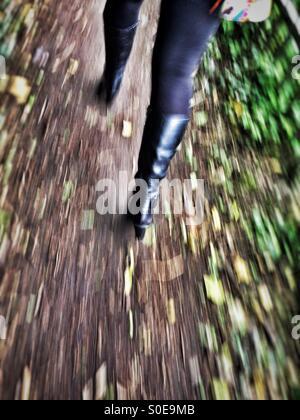 Desenfoque de movimiento de la hembra adulta de piernas con botas se aleja rápidamente a lo largo de un camino rural Foto de stock
