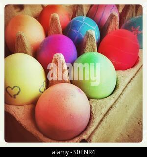 Huevos duros de colores brillantes en un cartón de huevos.