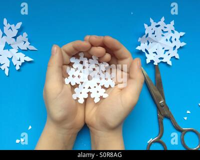 Niño contiene copos de nieve de papel Foto de stock