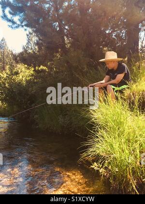 Joven vistiendo un sombrero de paja y la pesca desde la orilla del río Foto de stock