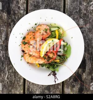 Mirando de arriba abajo en una fuente de marisco con gambas frescas en sus conchas y hojas de ensalada en un restaurante Foto de stock