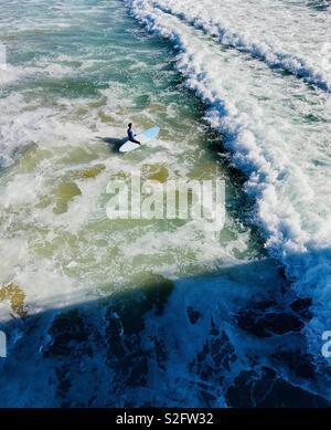 Un surfista masculino sale en el surf. Manhattan Beach, California, EE.UU. Foto de stock