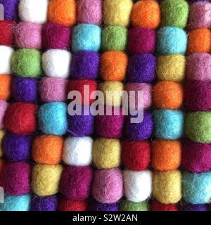 Un primer plano de muchas coloridas bolas de lana alineadas en filas y columnas