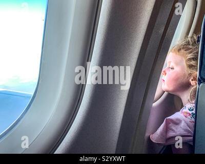 Joven en busca de un avión mientras volaba de ventana