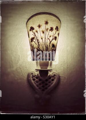 Still life: Una foto de un sucio viejo encendido Lampara de pared ingenio florido sombra en tono sepia echando una luz cálida. Foto de stock