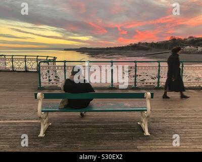 Dos señoras en Penarth pier al atardecer, caminar y leer un libro, Gales del Sur, en diciembre. Foto de stock