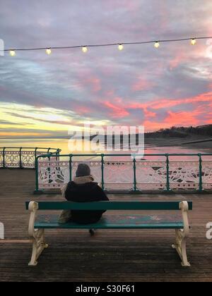 Una dama disfrutando de la puesta de sol desde Penarth pier mientras lee un libro, Gales del Sur, en diciembre. Foto de stock