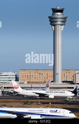 Los aviones en la pista con la torre de control en el fondo en el aeropuerto de Haneda, Tokio.