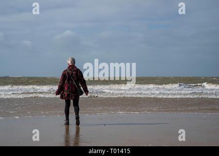 Una anciana detrás de paseos por la playa por el mar Foto de stock