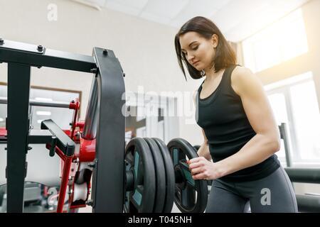 Hermosa mujer morena joven atlético haciendo ejercicios de fitness en el gimnasio. Fitness, deporte, formación, personal, concepto de estilo de vida saludable