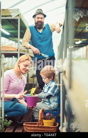 Concepto de educación informal. Chico plantando semillas con sus padres. Cute kid celebración hot pink pot mientras su madre tiene la cuchilla y el papá lleva la horquilla de jardinería