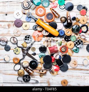 Carretes de hilos y botones en la mesa de madera.La Tijera cosiendo botones e hilo