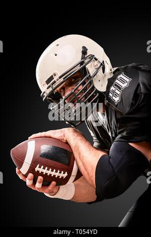 Retrato de jugador de fútbol americano sosteniendo un balón con ambas manos