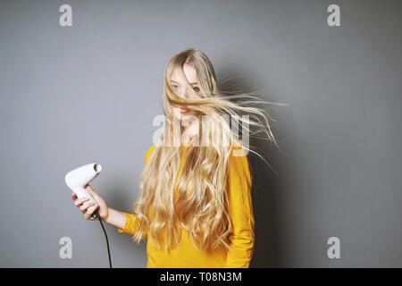 joven rubia soplando-secando su cabello