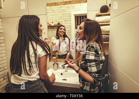 Las mujeres jóvenes son excitados haciendo maquillaje en el baño. Tienen un gran fin de semana en buena compañía en interiores. Foto de stock