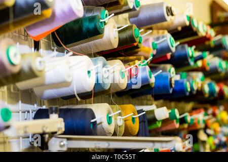 Cerca de coloridos Hilos de costura en el cajón. Closeup Shot de multicolores bobinas de hilo, accesorios de costura en Atelier.El enfoque selectivo.costura