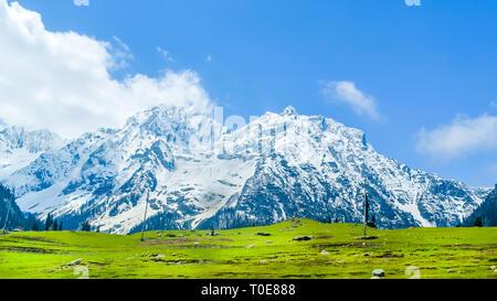 Amplia vista panorámica de picos de montañas cubiertos de nieve y el cielo azul con nubes en el valle Baisaran Mini (Suiza), Pahalgam, Cachemira, India