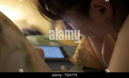 Joven Mujer hermosa en la cama hasta tarde en la noche por mensajería de texto a través de teléfono móvil somnoliento y cansado en la comunicación a través de internet uso excesivo concepto Foto de stock