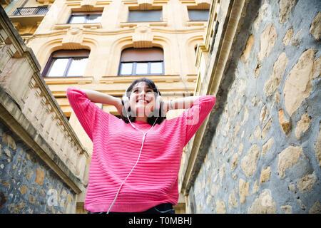 Feliz joven en rosa sweater escuchando música en la calle. Ángulo de visión baja Foto de stock