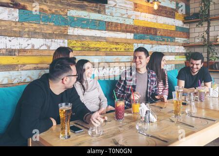 Feliz grupo de mejores amigos divirtiéndonos juntos en el pub de moda