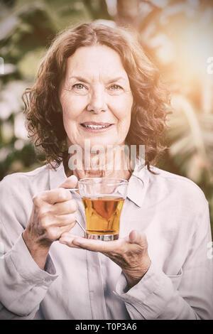 Sonriente mujer madura beber té de hierbas Foto de stock