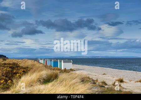 Playa de Findhorn Moray Firth Escocia chalets de color o cabañas de playa en Pebble Beach nieve por encima de las colinas y Black Isle
