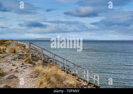 Playa de Findhorn Moray Firth Escocia una escalera de madera que conduce al Mar Negro y la isla más allá de la nieve en las montañas