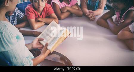 Maestro libro de lectura a los niños mirar su
