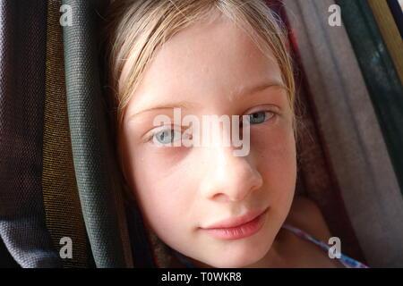 Retrato de una joven chica rubia mojada con ojos azules contently descansando en una hamaca