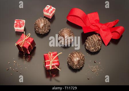 Pralines trufas de chocolate para el día de Navidad en color rosa y rojo con rojo atado arco. Dos pequeños props caja cuadrada de navidad regalo. Decoración festiva.