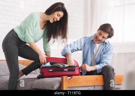 Par intentando cerrar la maleta completa en dormitorio