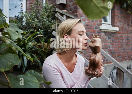 Mujer joven sentada en las escaleras de madera besos príncipe rana