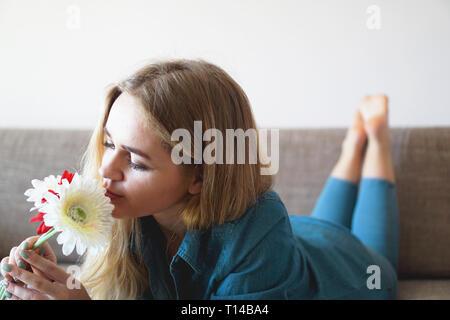Atractiva mujer joven sniffing ramo de flores tumbado en la cama Foto de stock