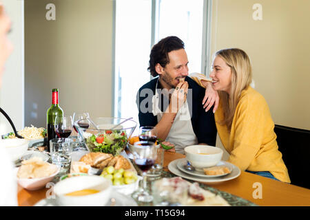 Amigos divirtiéndose, comiendo juntos, pareja de coquetear en la mesa