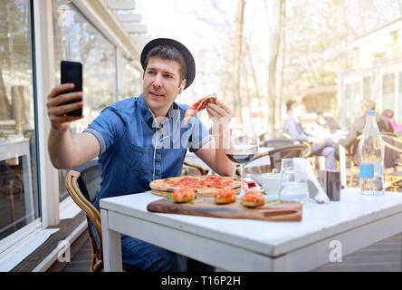 Solo el hombre tomando selfie turística y comer una porción de pizza en el restaurante italiano