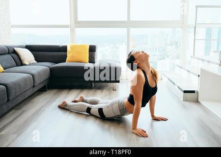 Mujer practicando Yoga en casa haciendo rutina Sun Salutation Foto de stock