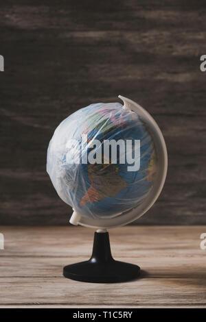 Primer plano de un globo terráqueo envuelto en plástico, sobre una tabla de madera rústica blanca contra un fondo gris rústico