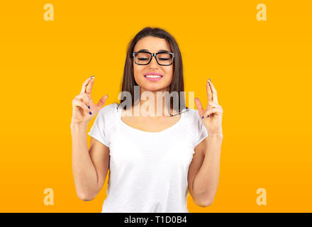 Lindo joven cruzar los dedos y que quieran una buena suerte aislado sobre fondo amarillo