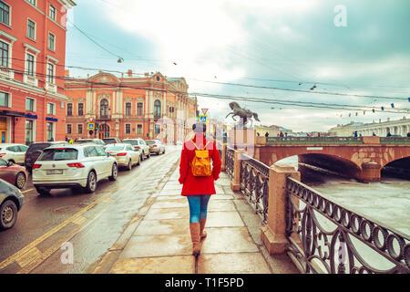 Rubia en una chaqueta roja paseos a lo largo de la orilla del río Fontanka. San Petersburgo, Rusia - 15 de marzo de 2019.