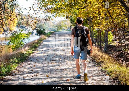 Hombre joven fotógrafo volver caminando por senderos camino trazado durante el otoño río Potomac en Great Falls, en el estado de Maryland, con un colorido follaje y mochila trípode Foto de stock