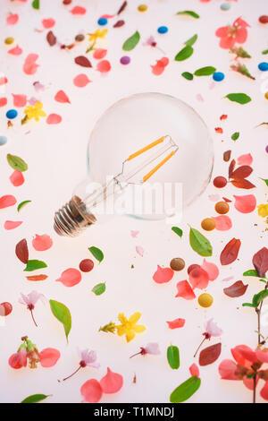 Bombilla de luz de creatividad y nuevas ideas sobre el concepto primavera arreglo floral de coloridos pétalos y hojas